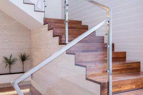 Eine Holztreppe mit einem eleganten Geländer aus Glas und Metall