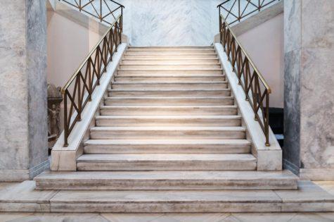 Eine Steintreppe mit Metallgeländer für ein grosses Treppenhaus