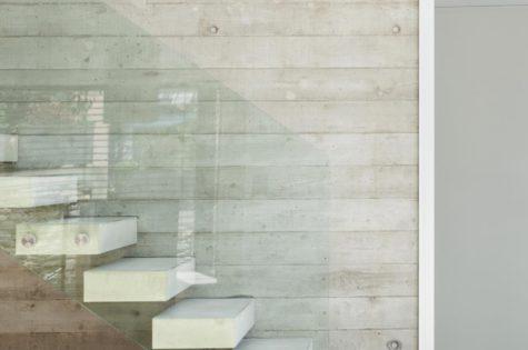 Eine moderne Treppe aus Beton mit einem Glasgeländer
